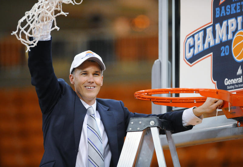 Florida Gulf Coast coach Andy Enfield holds up the net after his team defeated Mercer in an NCAA college basketball game for the Atlantic Sun men's tournament championship, in Macon, Ga., Saturday, March 9, 2013. Florida Gulf Coast won 88-75. (AP Photo/Woody Marshall)