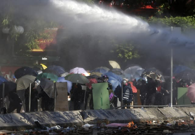 Protesters shelter with umbrellas as an armoured police vehicle sprays them with water
