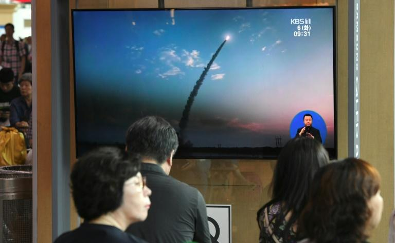 People watch a television news screen showing a file footage of North Korea's missile launch, at a railway station in Seoul on August 6, 2019