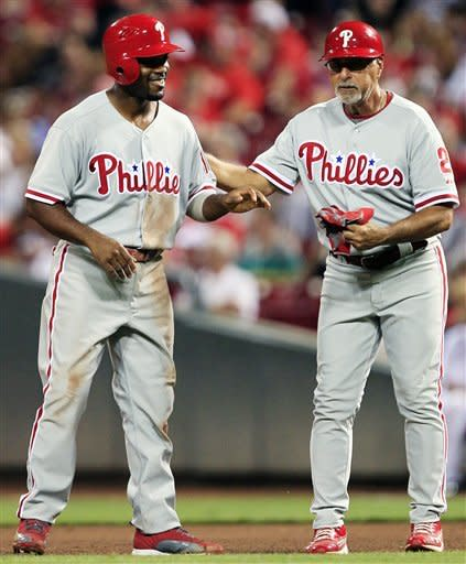 Philadelphia Phillies first base coach Sam Perlozzo (2) pats Jimmy Rollins on the back after Rollins hit a double for his 2,000th career hit in the fifth inning of a baseball game against the Cincinnati Reds, Tuesday, Sept. 4, 2012, in Cincinnati. (AP Photo/Al Behrman)