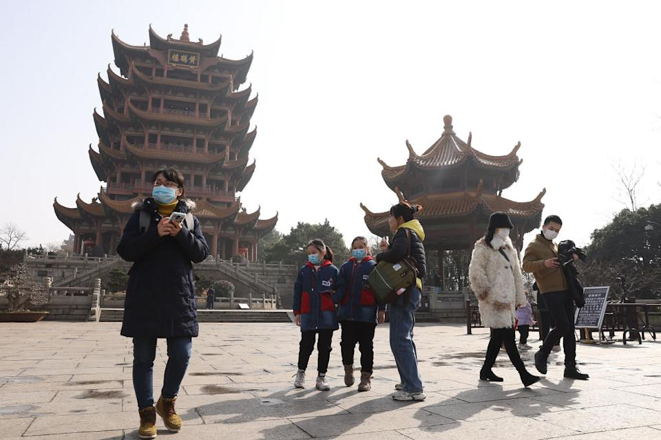 People wearing face masks visit the Yellow Crane Tower on January 28, 2021 in Wuhan, China.