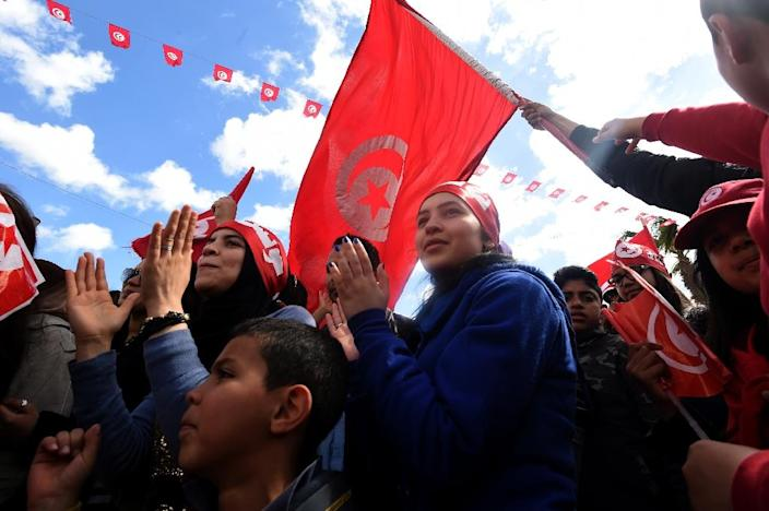 Tunisians wave their national flag and chant slogans during a march against extremism outside Tunis' Bardo Museum on March 29, 2015 (AFP Photo/Fethi Belaid)
