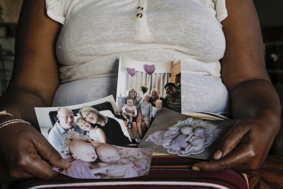 FILE - In this Sept. 17, 2021, file photo, Mandy Sibanyoni, nanny of the three daughters of Graham and Lauren Dickason, holds photographs of the Dickason family in her home in Pretoria, South Africa. People in the town of Timaru are planning an evening vigil outside the home of three young girls, Thursday, Sept. 23, 2021, who were killed last week in a crime that shocked New Zealand. The girls' mother Lauren Dickason has been charged with murder. (AP Photo/Sebabatso Mosamo, File)
