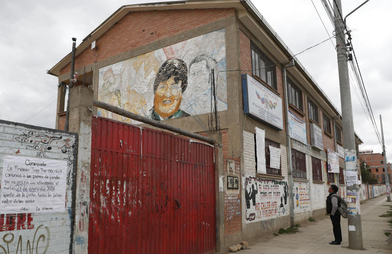 In this Jan. 18, 2020 photo, a man looks at a mural of Bolivia's former President Evo Morales painted on a wall of the Republic of Russia school in El Alto, Bolivia. While attempting to erase the images and statues of hated former leaders is often greeted by broad social consensus in other countries, it is facing backlash in Bolivia where Morales still has supporters, especially among indigenous peoples. (AP Photo/Juan Karita)