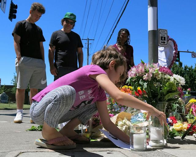 <p>Coco Douglas, 8, leaves a handmade sign and rocks she painted at a memorial in Portland, Ore., on Saturday, May 27, 2017, for two bystanders who were stabbed to death Friday while trying to stop a man who was yelling anti-Muslim slurs and acting aggressively toward two young women. From left are Coco's brother, Desmond Douglas; her father, Christopher Douglas; and her stepmother, Angel Sauls. (AP Photo/Gillian Flaccus) </p>