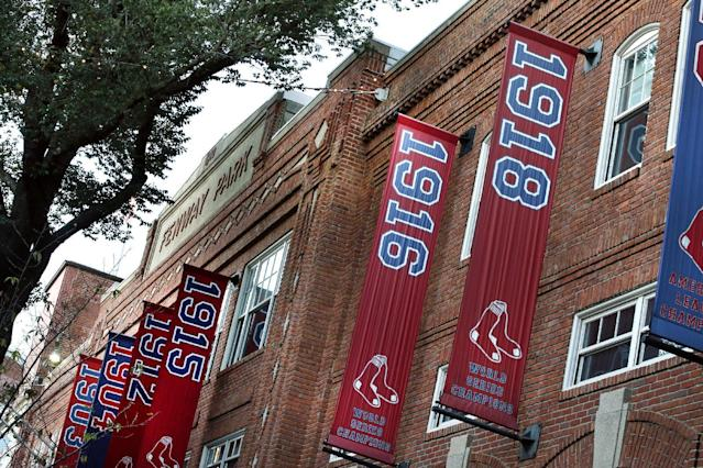 Championship banners hang on the facade of Fenway Park in Boston on Tuesday, Oct. 29, 2013, including the one from 1918, which was the last World Series that the Boston Red Sox clinched at home. The Red Sox will face the St. Louis Cardinals in Game 6 of the World Series on Wednesday in Boston. (AP Photo/Elise Amendola)