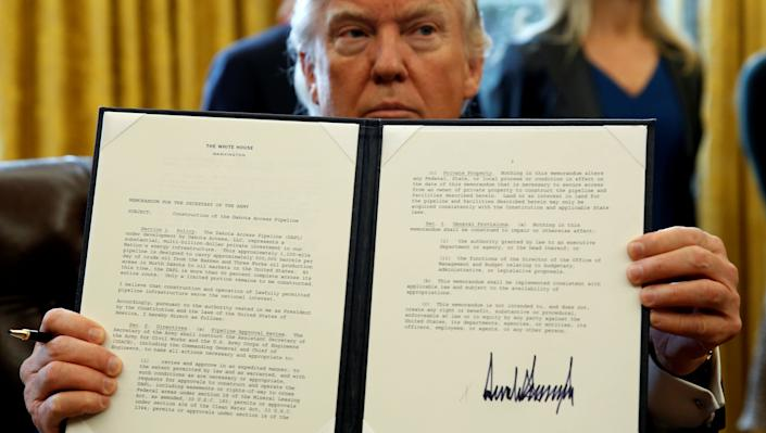 President Donald Trump holds up a signed executive order to advance construction of the Dakota Access pipeline at the White House on Jan. 24, 2017. (Photo: Kevin Lamarque/Reuters)