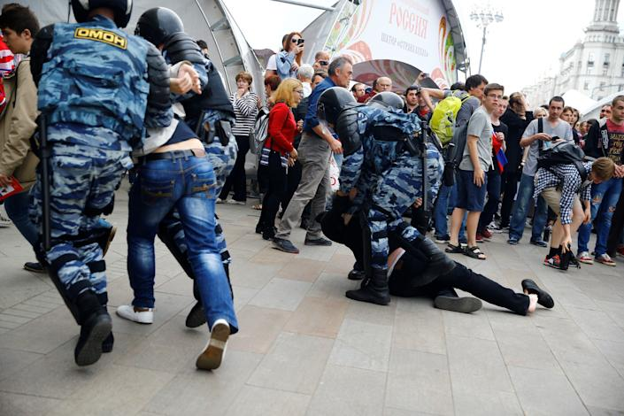 Russian police officers take a protester into custody.