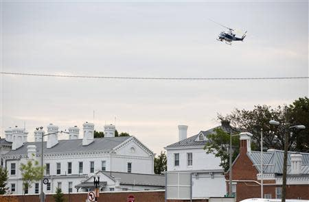 A police helicopter flies over the Washington Navy Yard as police respond to a shooting, in Washington September 16, 2013. REUTERS/Joshua Roberts
