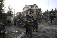 Afghan security personnel inspect around a damaged building following an attack in Kabul, Afghanistan, Wednesday, Aug. 4, 2021. A powerful explosion rocked an upscale neighborhood of Afghanistan's capital Tuesday in an attack that apparently targeted the country's acting defense minister. (AP Photo/Rahmat Gul)