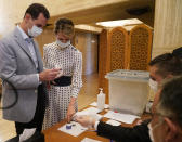 FILE - This file photo released July. 19, 2020 on the official Facebook page of Syrian Presidency, shows Syrian President Bashar Assad, left, and his wife Asma voting at a polling station in the parliamentary elections, in Damascus, Syria. The office of Syrian President Bashar Assad said Monday, March 8, 2021 that Assad and his wife have tested positive for the coronavirus and are both doing well. In a statement, Assad's office said the first couple did PCR tests after they felt minor symptoms consistent with the COVID-19 illness. (Syrian Presidency via AP, File)