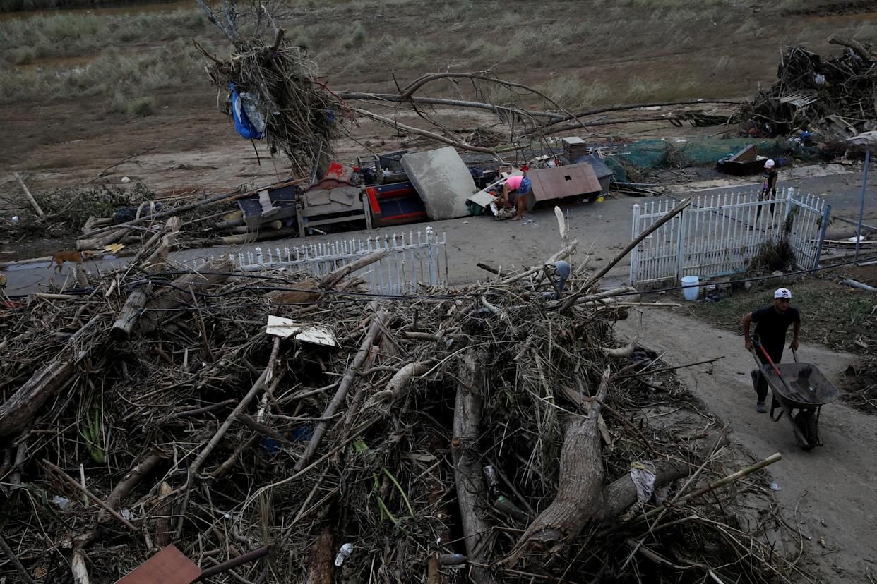 In Toa Baja, Puerto Rico, a woman searches for valuables among damaged belongings on the street, Sept. 24, 2017. (Photo: Carlos Garcia Rawlins/Reuters)