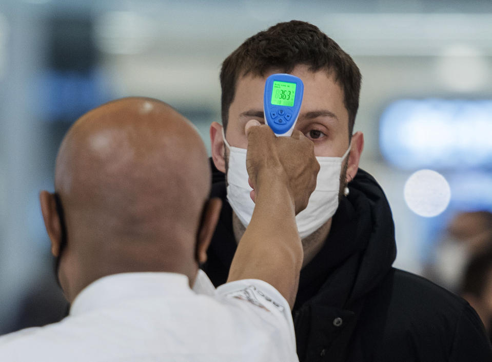 A man has his temperature checked prior to entering a store in Montreal, Sunday, Nov. 22, 2020, as the COVID-19 pandemic continues in Canada and around the world. (Graham Hughes/The Canadian Press via AP)