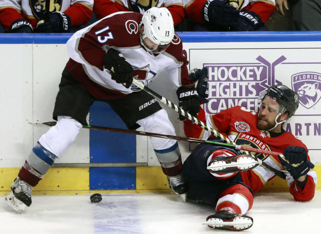 Colorado Avalanche center Alexander Kerfoot (13) and Florida Panthers defenseman Aaron Ekblad battle for the puck during the third period of an NHL hockey game, Thursday, Dec. 6, 2018 in Sunrise, Fla. (AP Photo/Wilfredo Lee)