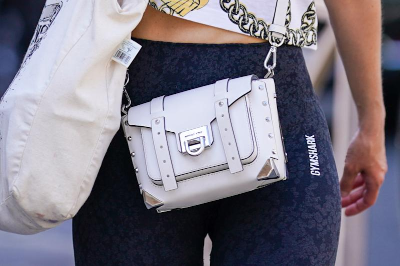 PARIS, FRANCE - JULY 09: A passerby wears Gymshark sportswear leggings, a Michael Kors white leather bag, a tote bag, on July 09, 2020 in Paris, France. (Photo by Edward Berthelot/Getty Images)