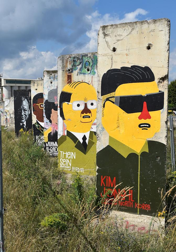 <p>Parts of the Berlin wall have been painted with the heads of politicians, like Kim Jong-il (R), in Teltow, Germany on August 8, 2016. (Bernd Settnik/EPA) </p>