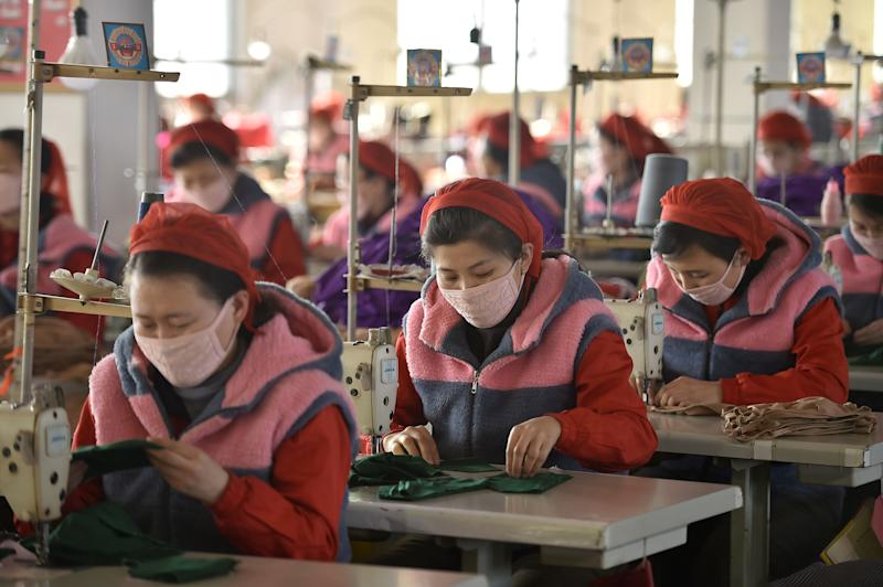 In this photo taken on February 6, 2020, workers of Songyo Knitwear Factory in Pyongyang produce masks for protection against the new coronavirus. - At least 31,000 people have been infected and more than 630 killed by the virus following the outbreak which began in the Chinese city of Wuhan, which has spread to two dozen countries. (Photo by Kim Won-Jin / AFP) (Photo by KIM WON-JIN/AFP via Getty Images)