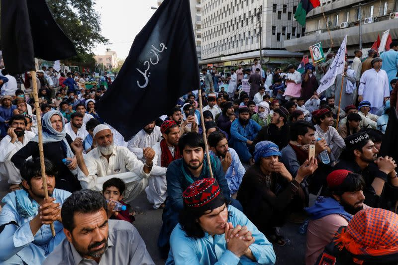 People sit with black flags as they demand an investigation following the deaths of four teenagers in Jani Khel area in Bannu District of Khyber Pakhtunkhwa (KPK) province, during a protest in Karachi,