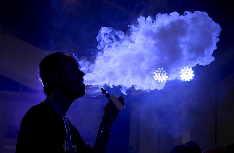 An exhibitor staff member uses an electronic cigarette at VAPE CHINA EXPO in Beijing