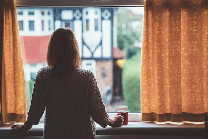 A former Sydney alcoholic has spoken of her addiction. Pictured is a stock image of woman at home staring through the window with a mug in hand.