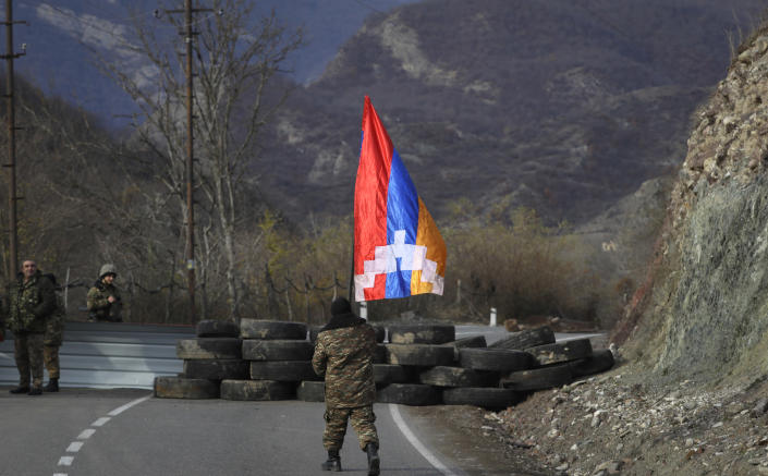 An ethnic Armenian soldier walks with Nagorno-Karabakh's flag towards a checkpoint near village of Charektar in the separatist region of Nagorno-Karabakh at a new border with Kalbajar district turned over to Azerbaijan, Wednesday, Nov. 25, 2020. The Azerbaijani army has entered the Kalbajar region, one more territory ceded by Armenian forces in a truce that ended deadly fighting over the separatist territory of Nagorno-Karabakh, Azerbaijan's Defense Ministry said Wednesday. The cease-fire, brokered by Russia two weeks ago, stipulated that Armenia hand over control to Azerbaijan of some areas its holds outside Nagorno-Karabakh's borders. (AP Photo/Sergei Grits)