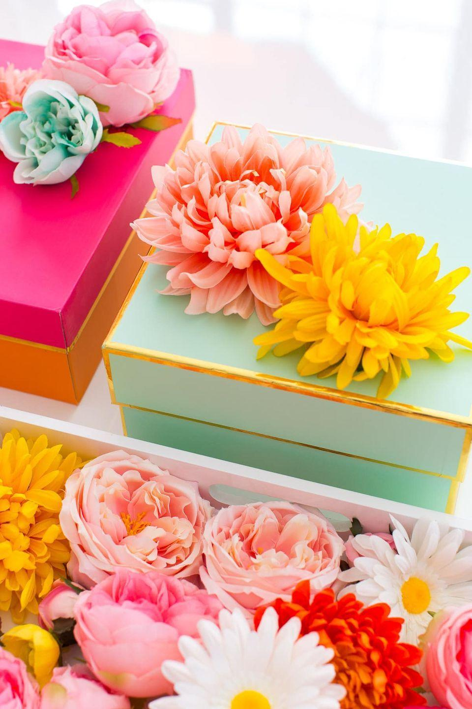 """<p>Out of wrapping paper? Create something just as stunning with a brightly-colored gift box topped with a lush faux flower. </p><p>Get the tutorial at <a href=""""https://sugarandcloth.com/diy-faux-flower-gift-topper-stickers/"""" rel=""""nofollow noopener"""" target=""""_blank"""" data-ylk=""""slk:Sugar and Cloth"""" class=""""link rapid-noclick-resp"""">Sugar and Cloth</a>.</p><p><a class=""""link rapid-noclick-resp"""" href=""""https://www.amazon.com/CQURE-Artificial-Hydrangea-Decoration-Champagne/dp/B07GZLGQ6T?tag=syn-yahoo-20&ascsubtag=%5Bartid%7C10072.g.34015639%5Bsrc%7Cyahoo-us"""" rel=""""nofollow noopener"""" target=""""_blank"""" data-ylk=""""slk:SHOP FAUX FLOWERS"""">SHOP FAUX FLOWERS</a></p>"""
