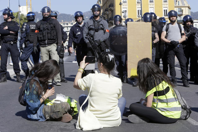Demonstrators sit in front of a police cordon during a protest in Nice, southeastern France, Saturday, March 23, 2019. The French government vowed to strengthen security as yellow vest protesters stage a 19th round of demonstrations, following last week's riots in Paris. (AP Photo/Claude Paris)