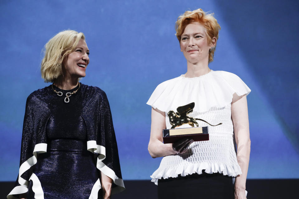 Actress Tilda Swinton, right, holds the Golden Lion for Lifetime Achievement, which was presented by Jury President Cate Blanchett during the opening ceremony of the 77th edition of the Venice Film Festival in Venice, Italy, Wednesday, Sept. 2, 2020. (AP Photo/Domenico Stinellis)