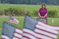 Sharon Grover stands over the grave of her daughter, Rachael, Tuesday, Sept. 28, 2021, at Fairview Cemetery in Mesopotamia, Ohio. Grover believes her daughter started using prescription painkillers around 2013 but missed any signs of her addiction as her daughter, the oldest of five children, remained distanced. (AP Photo/Tony Dejak)