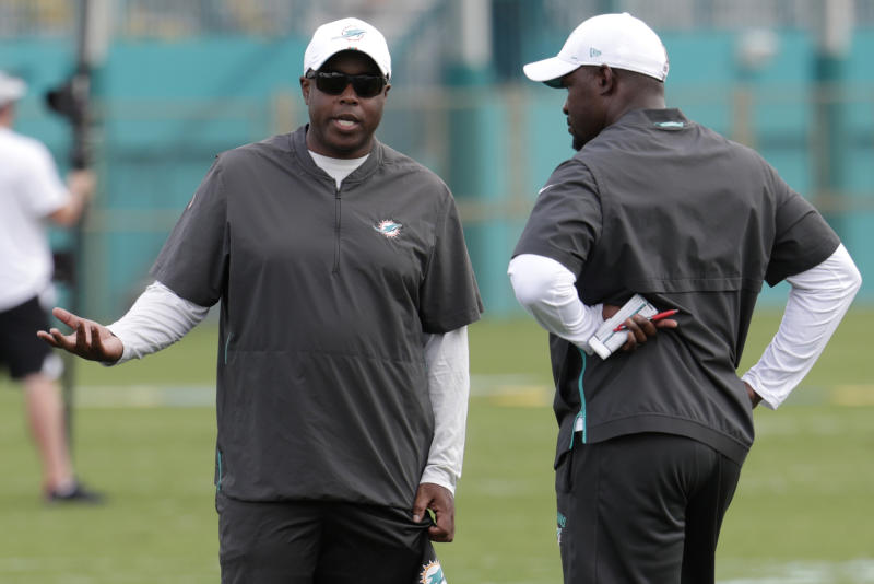 FILE - In this June 4, 2019, file photo, Miami Dolphins general manager Chris Grier, left, talks with head coach Brian Flores at the team's NFL football training facility, in Davie, Fla. Grier says this year's roster dismantling has been more drastic than he expected, but a turnaround can come quickly because the team will be aggressive in free agency in 2020. (AP Photo/Lynne Sladky, File)