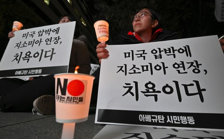 """South Korean protesters hold signs that read """"It is a disgrace to extend GSOMIA because of the pressure from the US"""""""