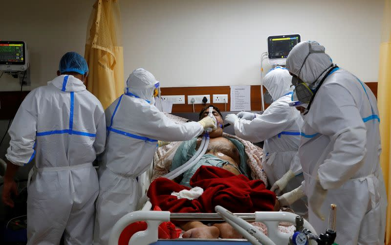 Medical workers take care of a patient suffering from the coronavirus disease (COVID-19), at a hospital in Noida