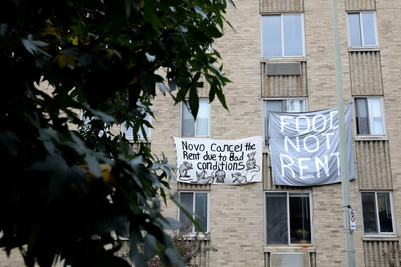 Makeshift sheets displaying messages of protest contesting the ability to pay for rent hang in a window of an apartment building in Washington