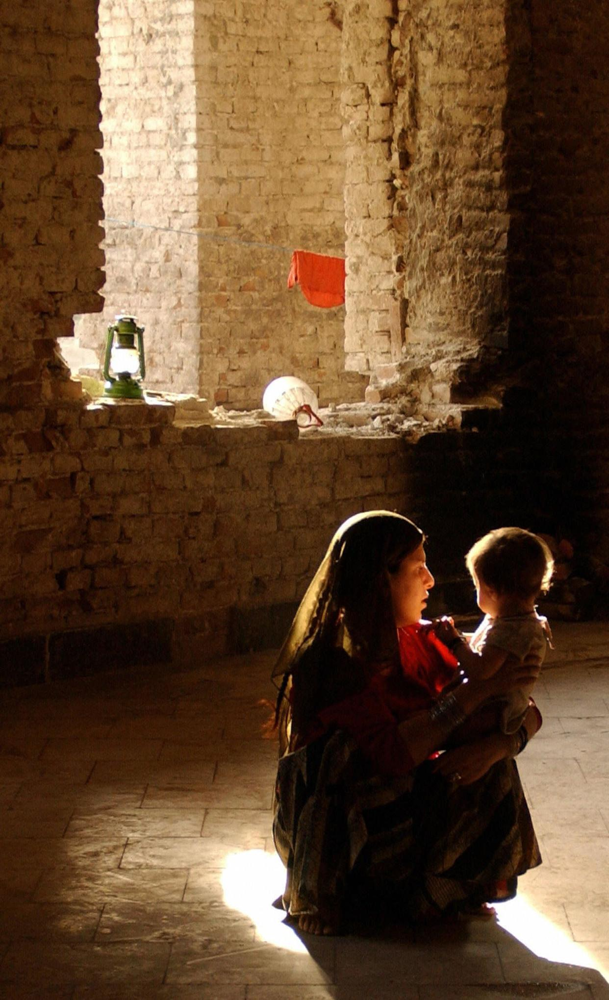 An Afghan refugee holds her child as she sits in the sunshine inside their home in Kabul, 02 October 2005.