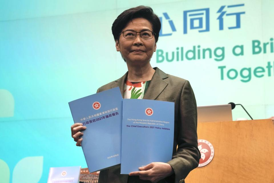 Hong Kong Chief Executive Carrie Lam holds copies of policies address during a news conference after delivering her policy address at the Legislative Council in Hong Kong, Wednesday, Oct. 6, 2021. Lam announced a major development plan Wednesday for Hong Kong's border area with mainland China in the last annual policy address of her current term. (AP Photo/Kin Cheung)