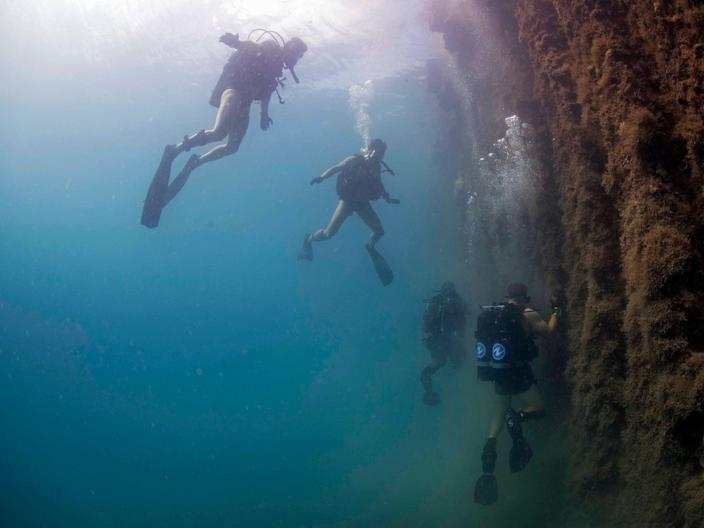 Members of the Royal Australian navy Clearance Diving Team observe as U.S. Navy Sailors assigned to Underwater Construction Team (UCT) 2 conduct a pier inspection in Apra Harbor, Guam,