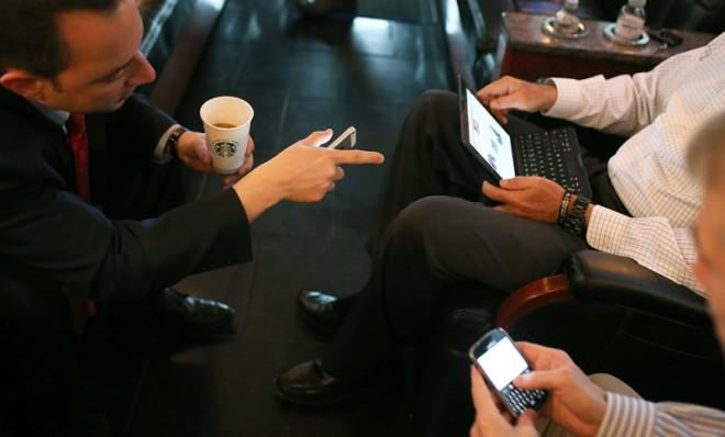 RNC Chairman Reince Priebus speaks to Mitt Romney and Rob Portman while each man uses his respective gadget.