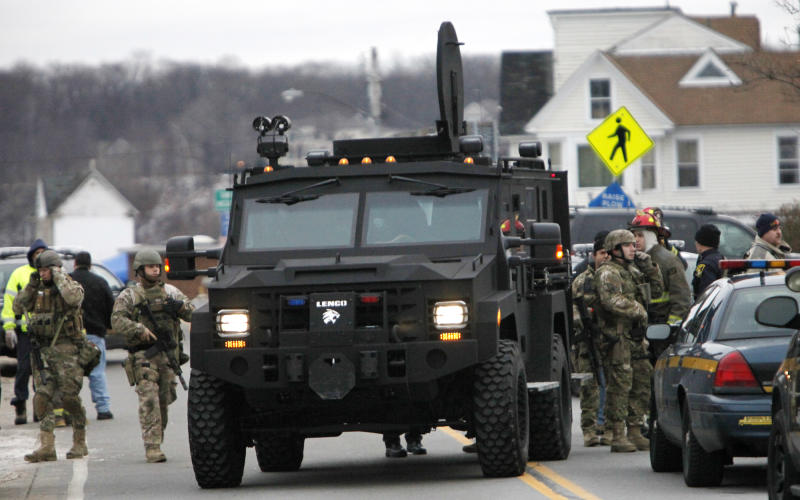 A Monroe County Sheriff's Department armored truck drops off residents who were evacuated from the neighborhood, Monday, Dec. 24, 2012 in Webster, New York. A former convict set a house and car ablaze in his lakeside New York state neighborhood to lure firefighters then opened fire on them, killing two and engaging police in a shootout before killing himself while several homes burned. Authorities used an armored vehicle to evacuate the area. (AP Photo/Democrat & Chronicle, Max Schulte)
