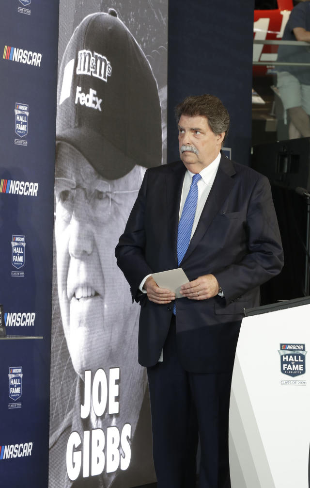 NASCAR vice chairman Mike Helton watches a video after naming team owner Joe Gibbs a member of the NASCAR Hall of Fame, in Charlotte, N.C., Wednesday, May 22, 2019. (AP Photo/Chuck Burton)