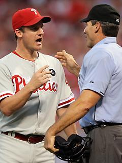 Phillies pitcher Roy Oswalt talks with home-plate umpire Angel Hernandez after a squirrel ran across home plate during a pitch