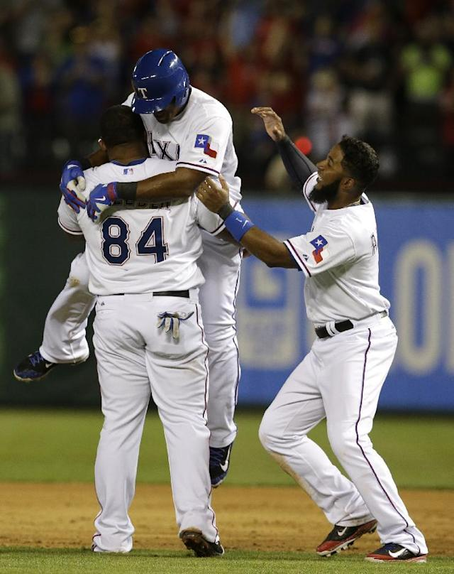 Texas Rangers' Prince Fielder (84) lifts Adrian Beltre, as Elvis Andrus, right, watches after Beltre hit a game-winning single off of Philadelphia Phillies relief pitcher B.J. Rosenberg in the ninth inning of a baseball game, Tuesday, April 1, 2014, in Arlington, Texas. The hit scored Shin-Soo Choo from second in the 3-2 Rangers win. (AP Photo/Tony Gutierrez)