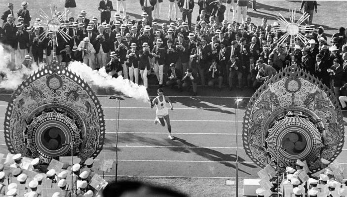 FILE - In this Oct. 10, 1964, file photo, Japanese runner Yoshinori Sakai carries the Olympic Torch during the opening ceremonies of the 1964 Summer Olympics in Tokyo. The famous 1964 Tokyo Olympics highlighted Japan's resiliency. It was a prospering country that was showing off bullet trains, transistor radios, and a restored reputation just 19 years after devastating defeat in World War II. Now Japan and Tokyo are on display again, attempting to stage the postponed 2020 Tokyo Olympics in the midst of a once-in-a century pandemic. (AP Photo, File)