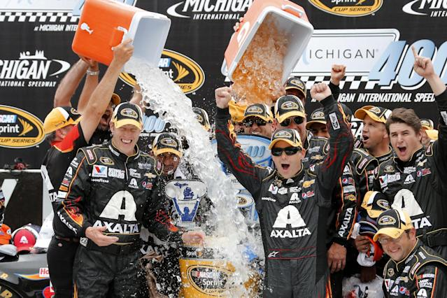 Jeff Gordon celebrates his victory with crew members after the NASCAR Sprint Cup Series Pure Michigan 400 auto race at Michigan International Speedway in Brooklyn, Mich., Sunday, Aug. 17, 2014. (AP Photo/Bob Brodbeck)