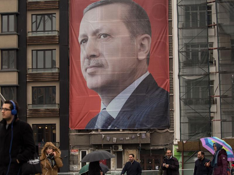 People walk past a large banner showing the portrait of Turkish President Recep Tayyip Erdogan in Taksim Square: Getty