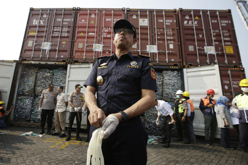 Director General of Indonesian Customs and Excise Heru Pambudi speaks to the press near containers full of plastic waste at Tanjung Priok port in Jakarta, Indonesia Wednesday, Sept. 18, 2019. Indonesia is sending hundreds of containers of waste back to Western nations after finding they were contaminated with used plastic and hazardous materials.  (AP Photo/Achmad Ibrahim)