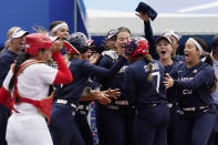 United States' Kelsey Stewart (7) is greeted at the plate by her teammates following her game winning home run against Japan in the seventh inning of a softball game at the 2020 Summer Olympics, Monday, July 26, 2021, in Yokohama, Japan. (AP Photo/Sue Ogrocki)