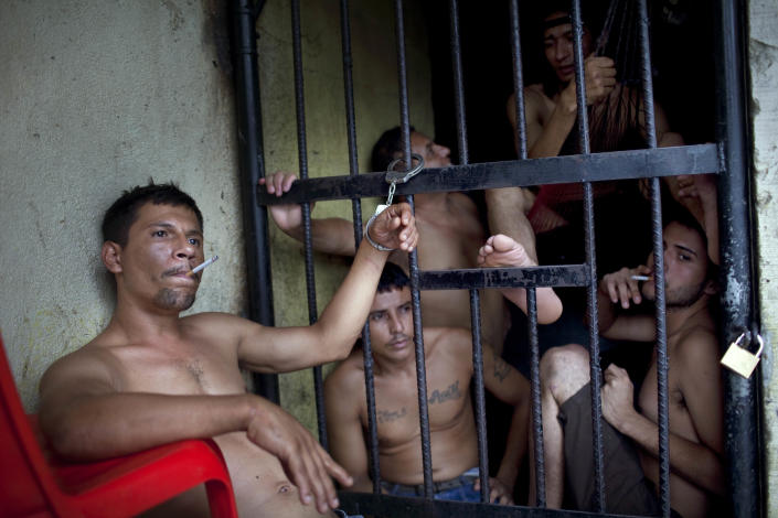 In this May 3, 2012 photo, an inmate, handcuffed to the bars of his cell as punishment for beating a guard, smokes a cigarette at the San Pedro Sula Central Corrections Facility in San Pedro Sula, Honduras. Inside one of Honduras' most dangerous and overcrowded prisons, inmates operate a free-market bazaar, selling everything from iPhones to prostitutes. Guards do not cross into the inner sanctum controlled by prisoners, and prisoners do not breach the perimeter controlled by guards. (AP Photo/Rodrigo Abd)