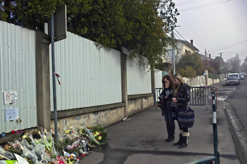 Women pay respects outside the Ozar Hatorah Jewish school, in Toulouse, France, Friday March 23, 2012 where three children and a rabbi were gunned down on Monday. Inspired by radical Islam and trained in Afghanistan, the gunman methodically killed French schoolchildren, a rabbi and paratroopers and faced down hundreds of police for 32 hours. Then he leapt out a window as he rained down gunfire and was fatally shot in the head. (AP Photo/Thibault Camus)