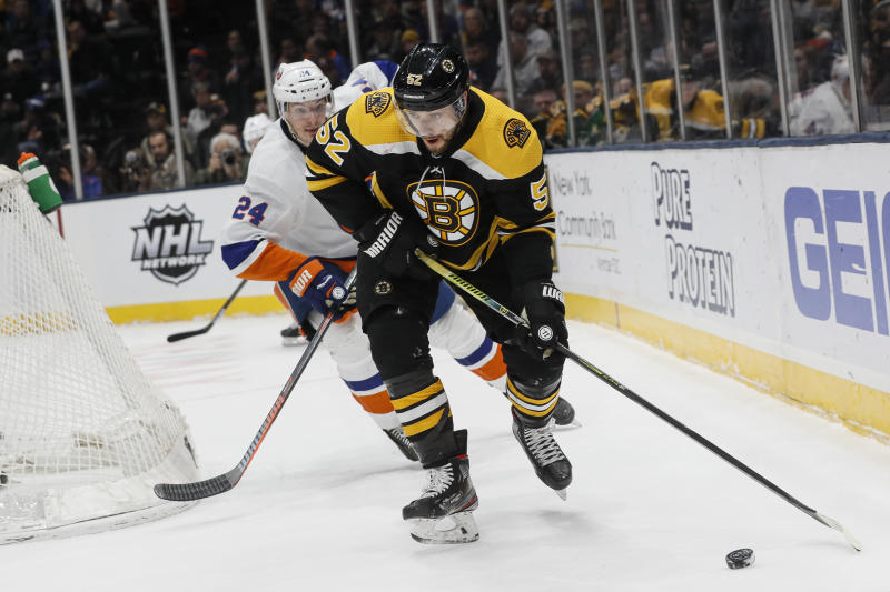 Boston Bruins center Sean Kuraly (52) skates the puck behind the New York Islanders net against defenseman Scott Mayfield (24) during the first period an NHL hockey game, Saturday, Feb. 29, 2020, in Uniondale, NY. (AP Photo/John Minchillo)