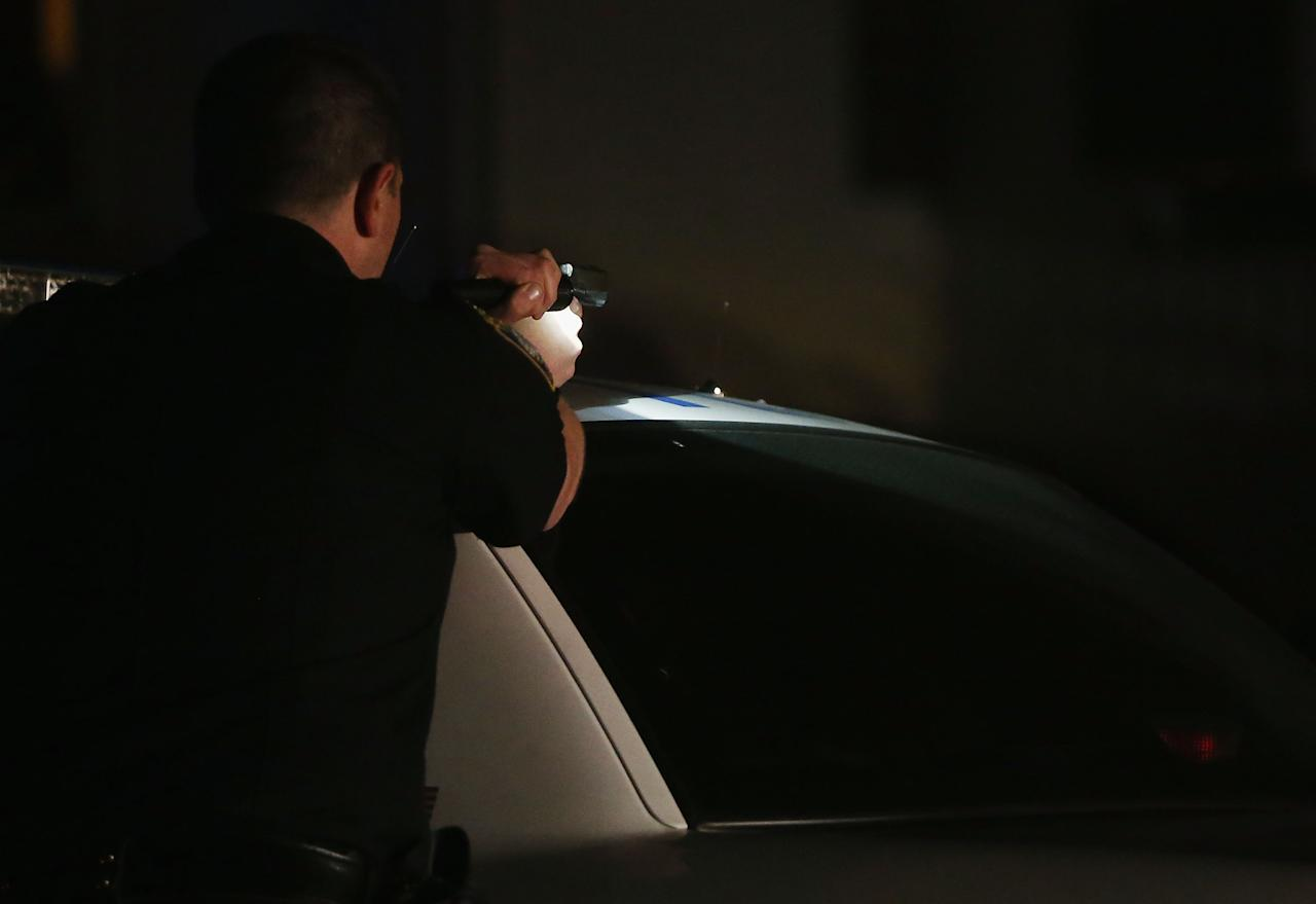 WATERTOWN, MA - APRIL 19:  A police officer with gun drawn and flashlight searches for a suspect on April 19, 2013 in Watertown, Massachusetts. Earlier, a Massachusetts Institute of Technology campus police officer was shot and killed late Thursday night at the school's campus in Cambridge. A short time later, police reported exchanging gunfire with alleged carjackers in Watertown, a city near Cambridge. According to reports, one suspect has been killed during a car chase and the police are seeking another - believed to be the same person (known as Suspect Two) wanted in connection with the deadly bombing at the Boston Marathon earlier this week. Police have confirmed that the dead assailant is Suspect One from the recently released marathon bombing photographs. (Photo by Mario Tama/Getty Images)